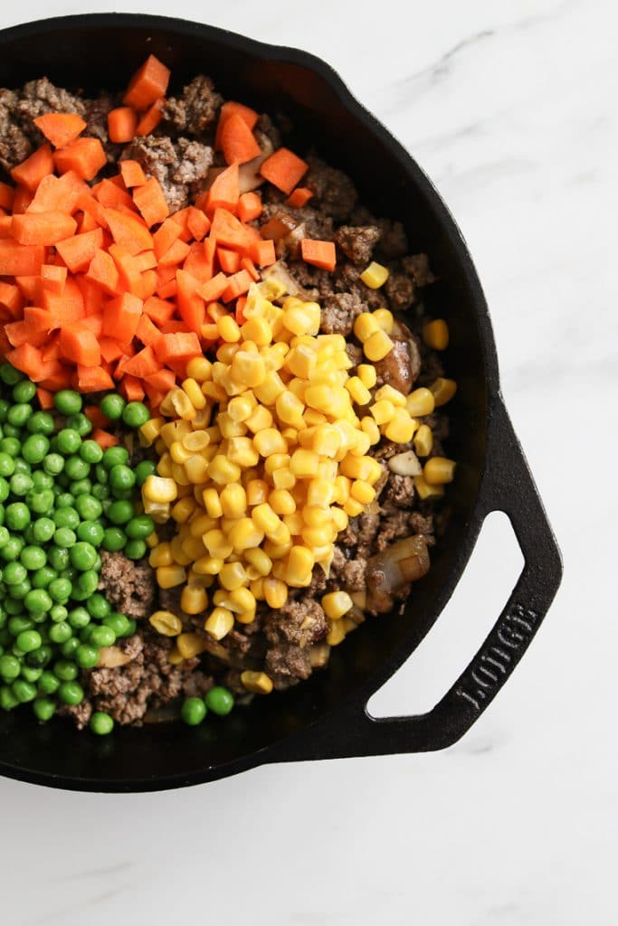 Diced carrots, corn, and peas added the cast iron skillet with browned beef for Beef Shepherd's Pie