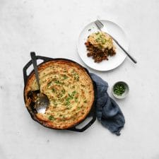 Beef Shepherd's Pie in a cast iron skillet next to a plate with a piece of shepherd's pie and small bowl of parsley