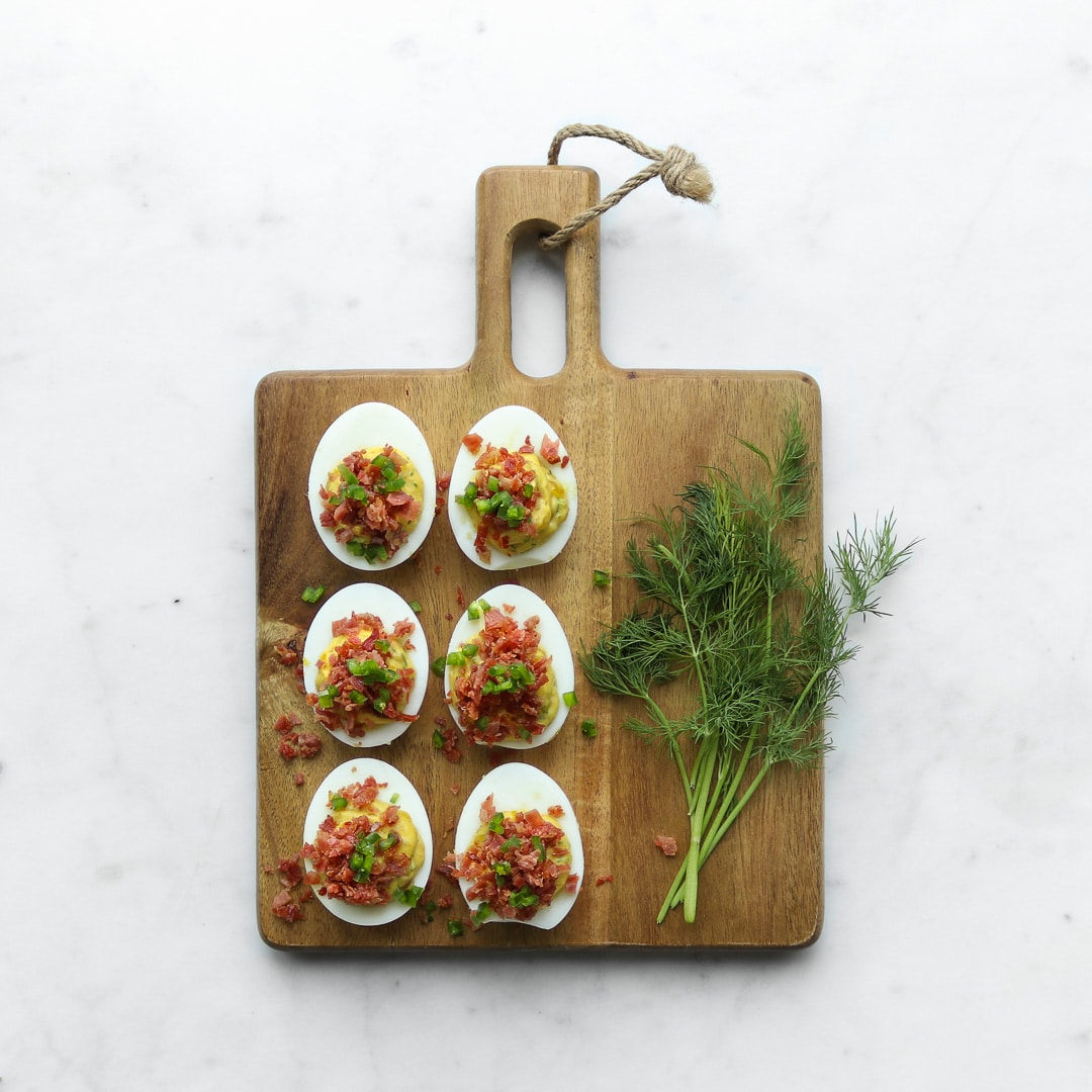 Six deviled eggs on a cutting board with a sprig of dill