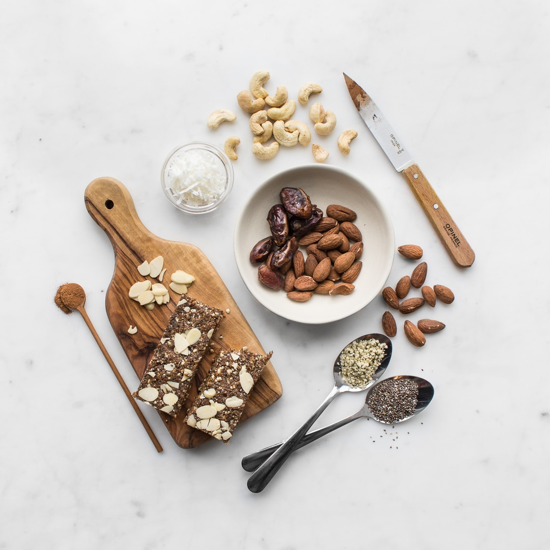 Flat lay image of nuts, seeds, coconut, cinnamon and styling props