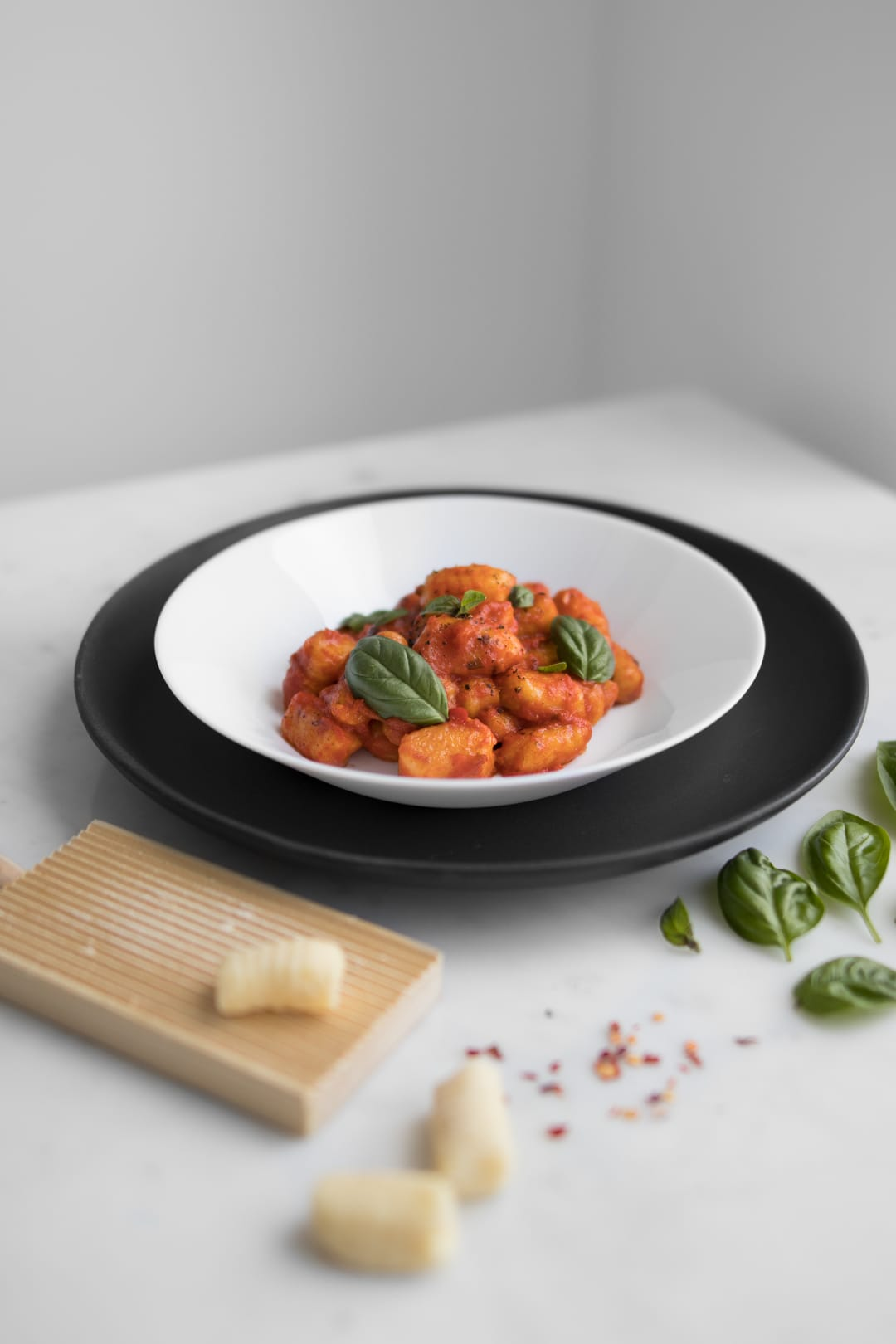 Gluten-free gnocchi with tomato sauce in a white bowl, on top of a black plate. Uncooked gnocchi and basil are placed around the plate. Get the recipe at chefsouschef.com
