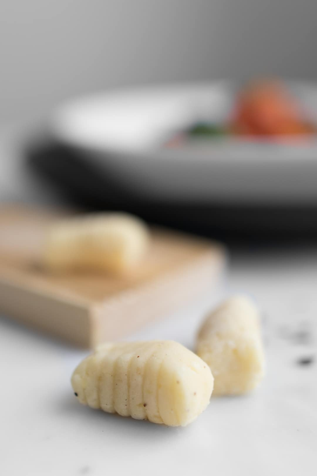 Uncooked gluten-free gnocchi with a gnocchi shaping board.
