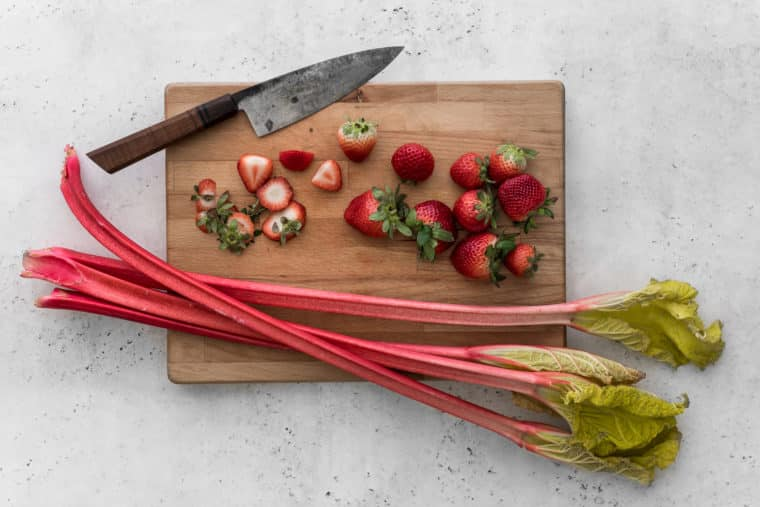 Chopped strawberries and rhubarb stalks on a cutting board with a knife