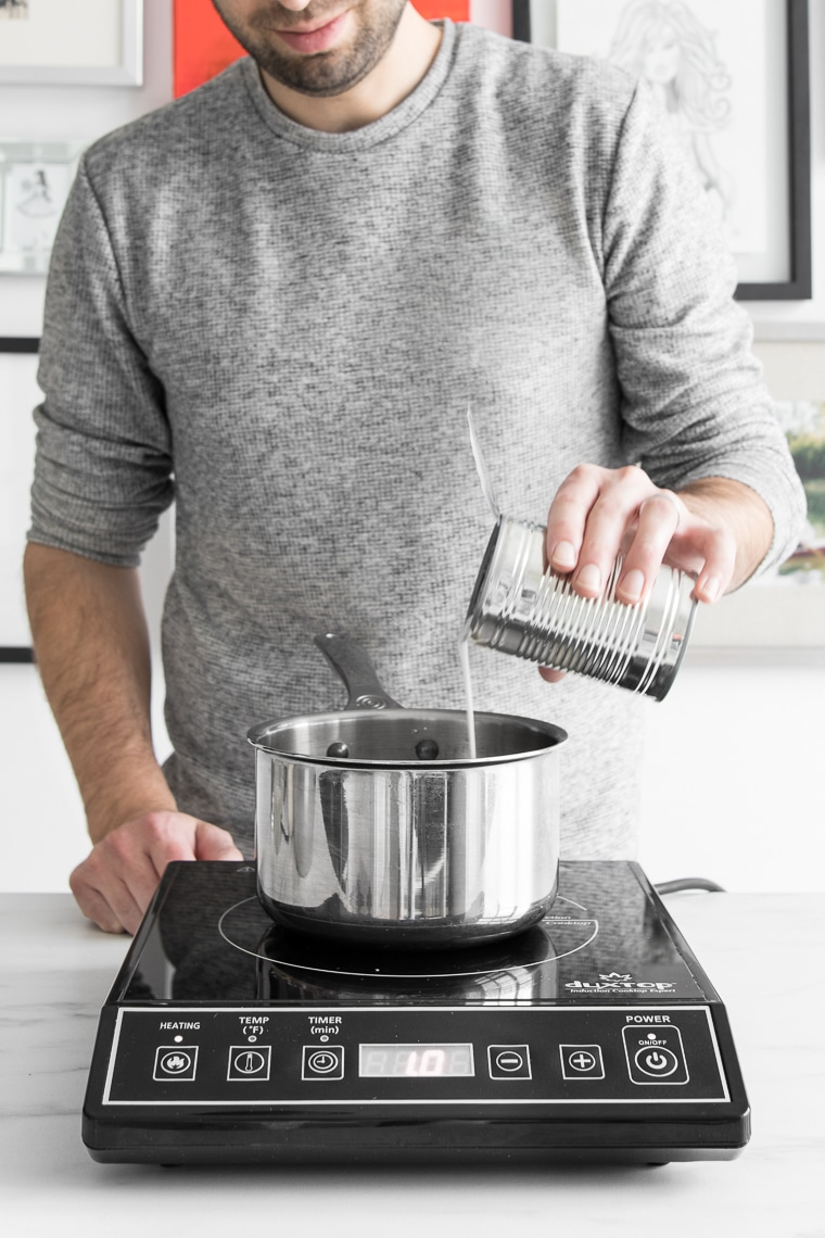 Pouring coconut milk into a saucepan