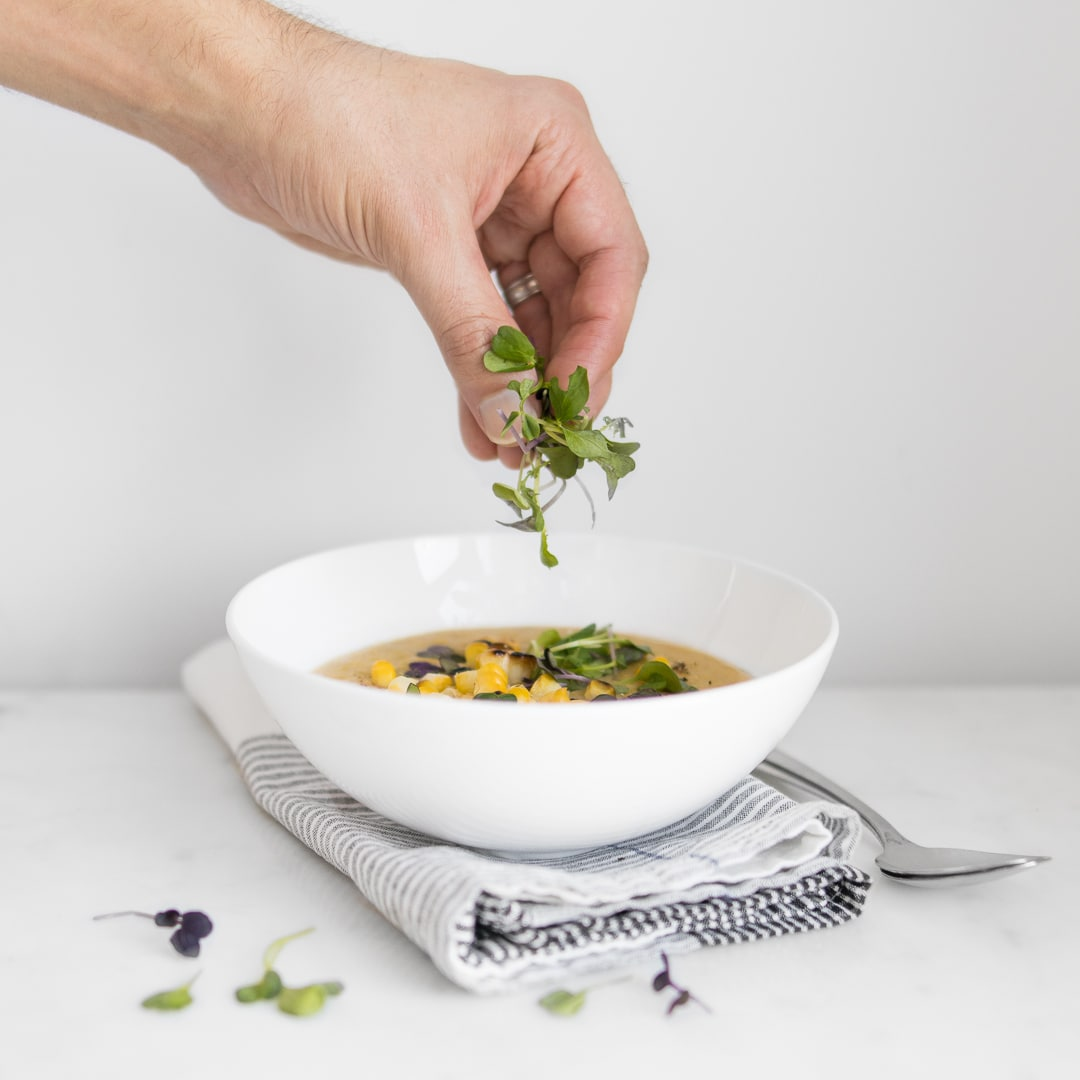 Hand garnishing the top of the soup with micro greens