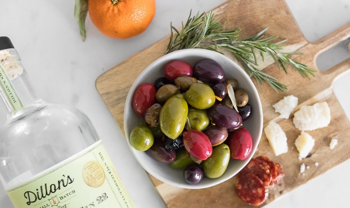 Colourful Warm Olives in a bowl, next to a bottle of gin laying on a marble table