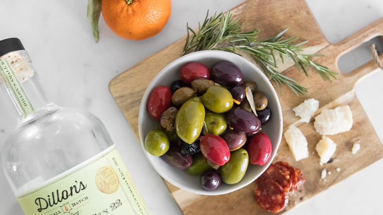 Close up image of Warm Olives with Citrus and Gin in a bowl, on charcuterie board with parmesan cheese, salami, an orange, and gin bottle