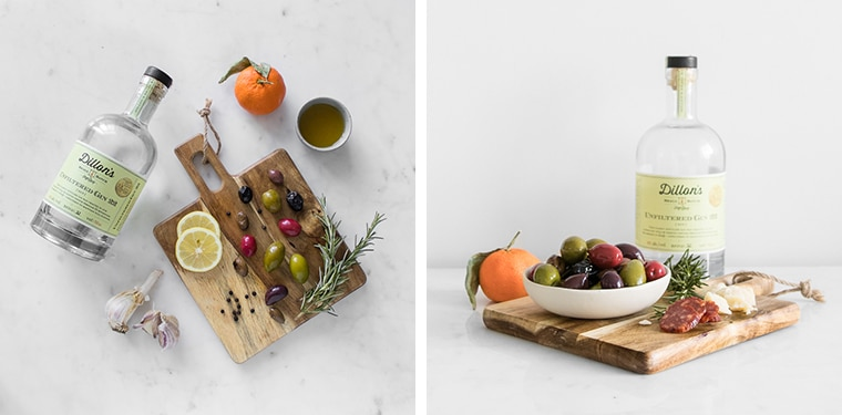 Flat lay image of ingredients for warm olives with citrus and gin and finished image of olives on a charcuterie board with a bottle of gin