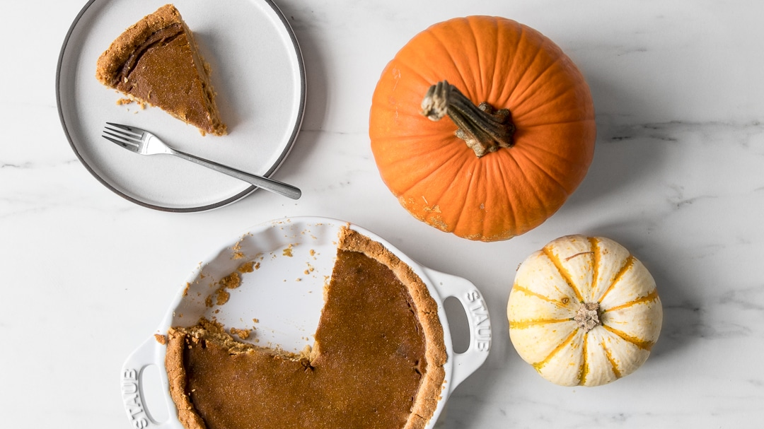 Whole30 Pumpkin Pie with slice out and on a plate next to two mini pumpkins