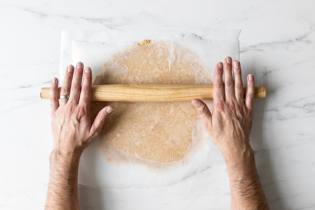 Rolling out a paleo pie dough between two sheets of parchment paper