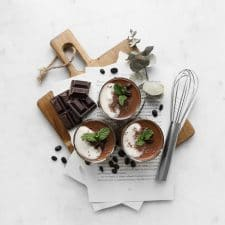 Three servings of chocolate coconut custard on a wood board with chocolate chunks, coffee beans, and a small whisk