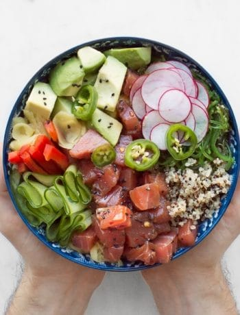 Hands holding a large bowl filled with raw tuna, cucumber ribbons, diced avocado, rice, radishes and jalapeño slices