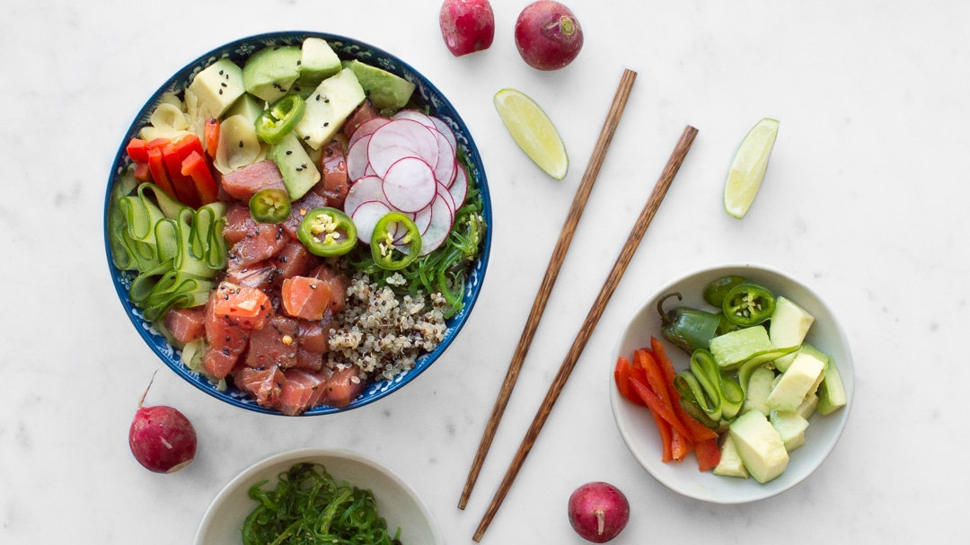 Poke bowl next to chopsticks and fresh vegetables