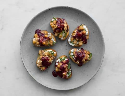 6 crostini topped with apples, cheese and berry sauce