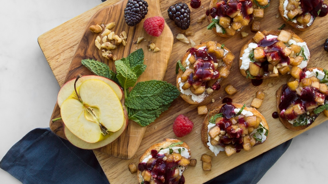 Apple Bruschetta on a wooden cutting board with apple slices