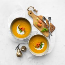 Two bowls of carrot and ginger soup styled with props