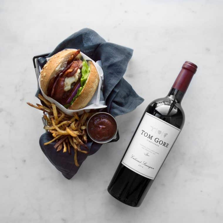 Burger on a blue napkin with fries, homemade ketchup and bottle of wine