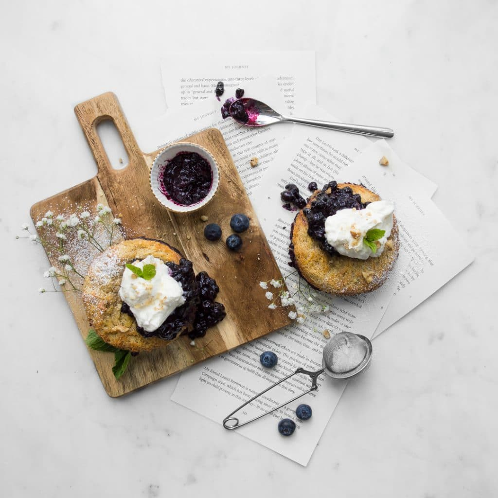 Flat lay of two mini Blueberry French Toast Cakes with whipped cream and blueberry sauce