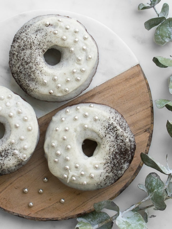 Three chocolate donuts with white frosting and silver balls on a wood and marble cutting board