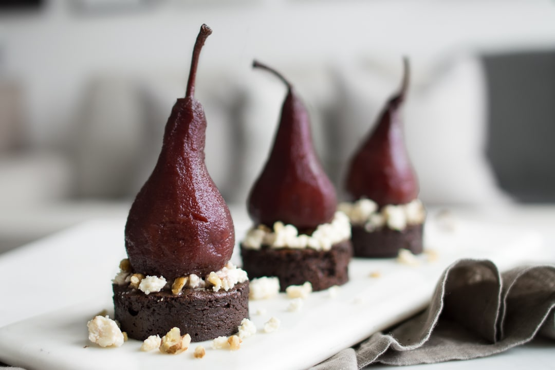 Three red poached pears on top of round chocolate cake with blue cheese crumble