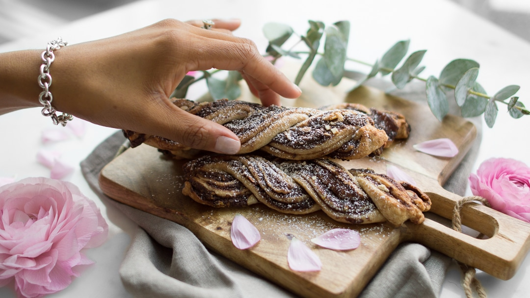 Hand picking up chocolate twist pastry