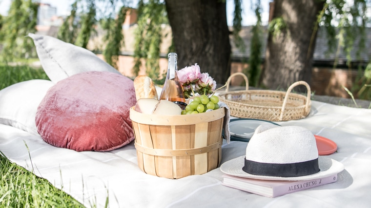 Park picnic scene with picnic blanket, pillows, basket of food and a hat.