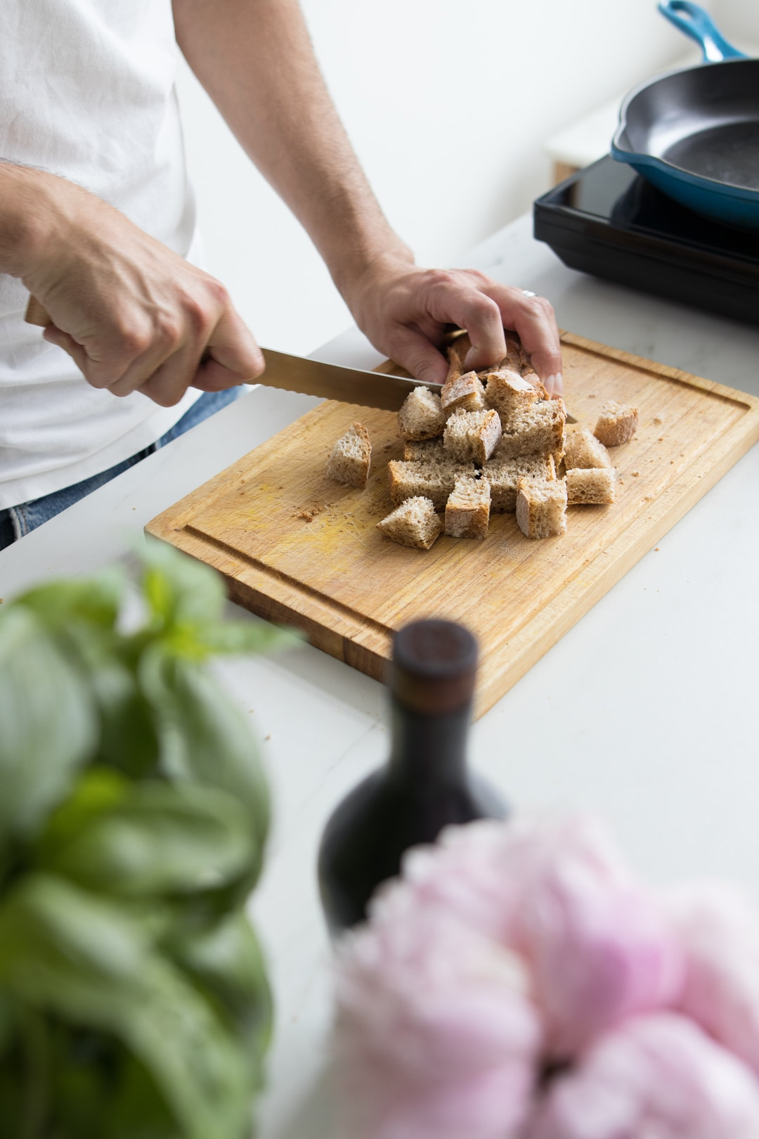 Male cutting bread into cubes on wooden cutting board surrounded by bottle, flowers, and basil