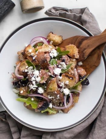 Close up of Fig Panzanella in a bowl with wooden spoons and a grey napkin