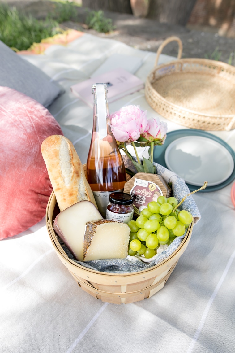 Basket with cheeses, grapes, baguette, jelly and rose champagne
