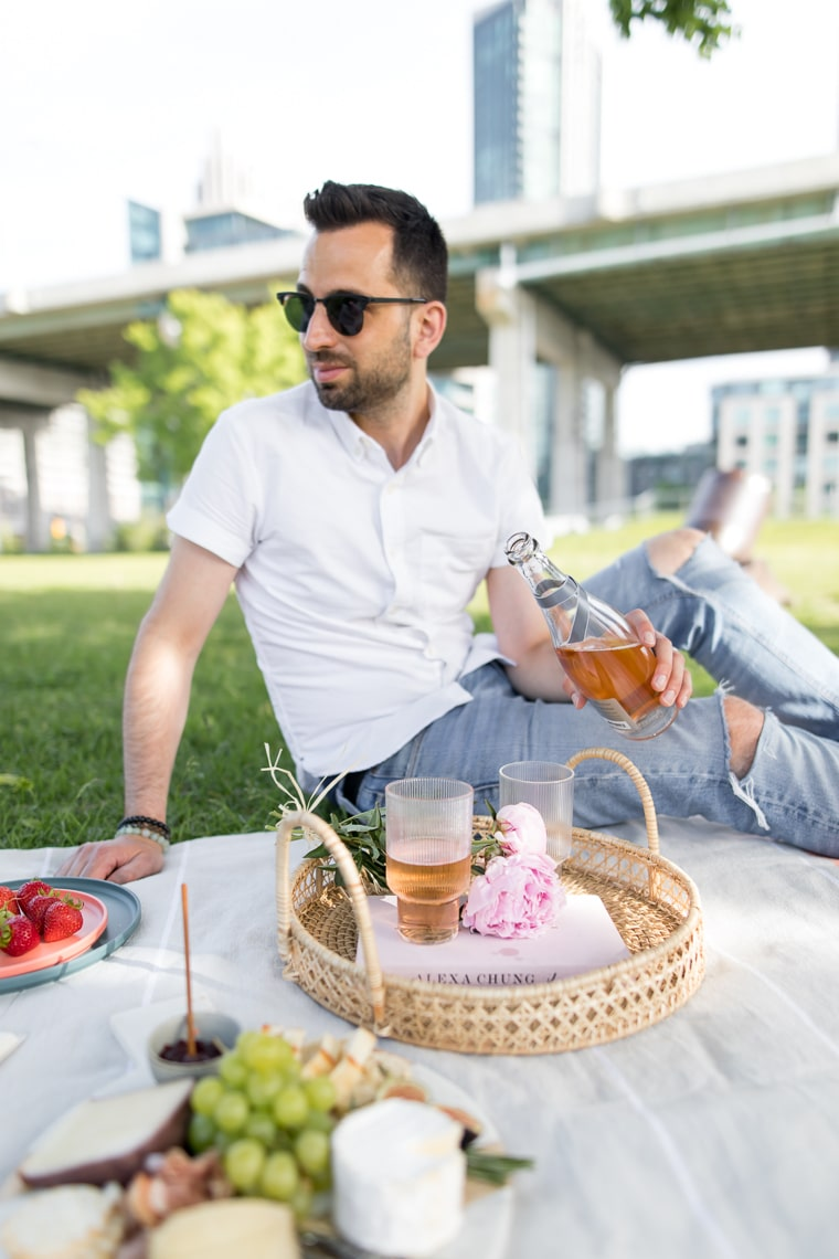Male pouring rose for a picnic in the city