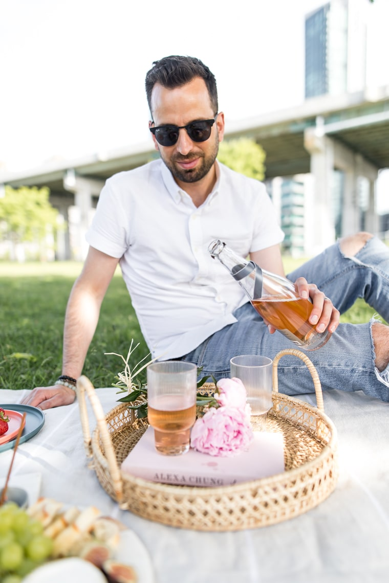 Male pouring rose champagne for a picnic