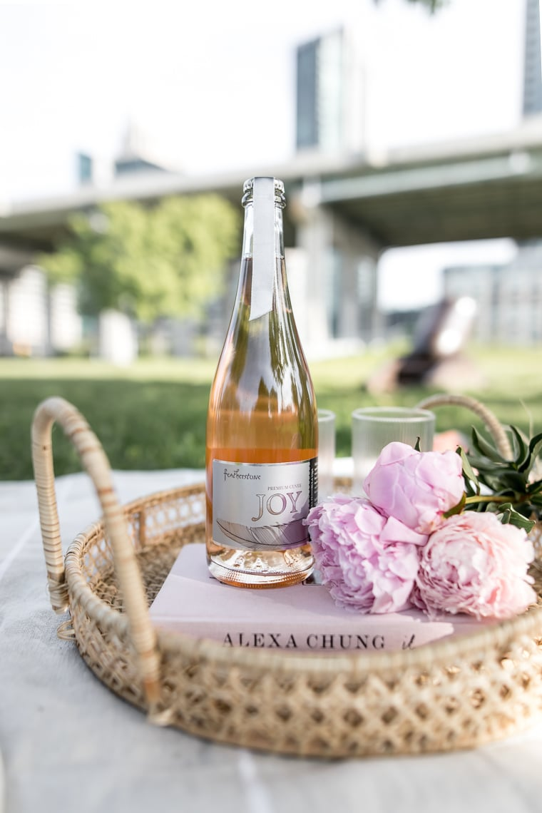 close up of wicker tray holding a book, pink peonies, and a bottle of rose prosecco