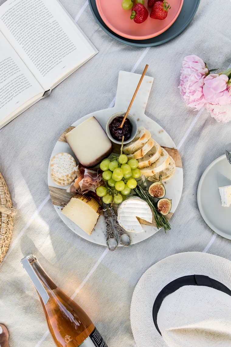 Marble board with cheeses, meats, grapes, and jelly on a blanket with a book and hat