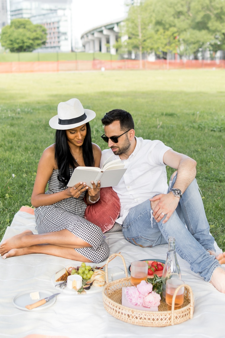 Couple reading a book together while having a picnic in the city