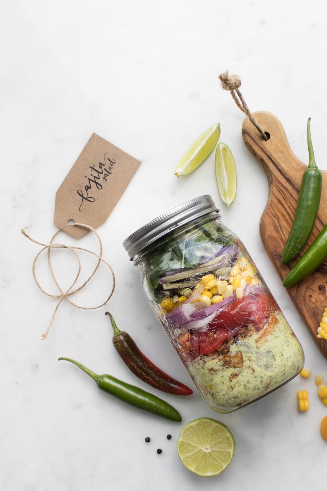Fajita Salad layered in a mason jar next to jalapeños, limes, and corn