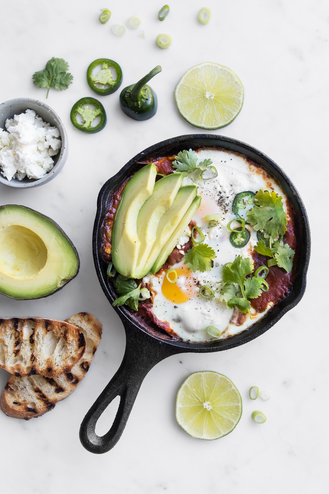 Close up of Mexican Shakshouka in a black skillet with sliced avocado