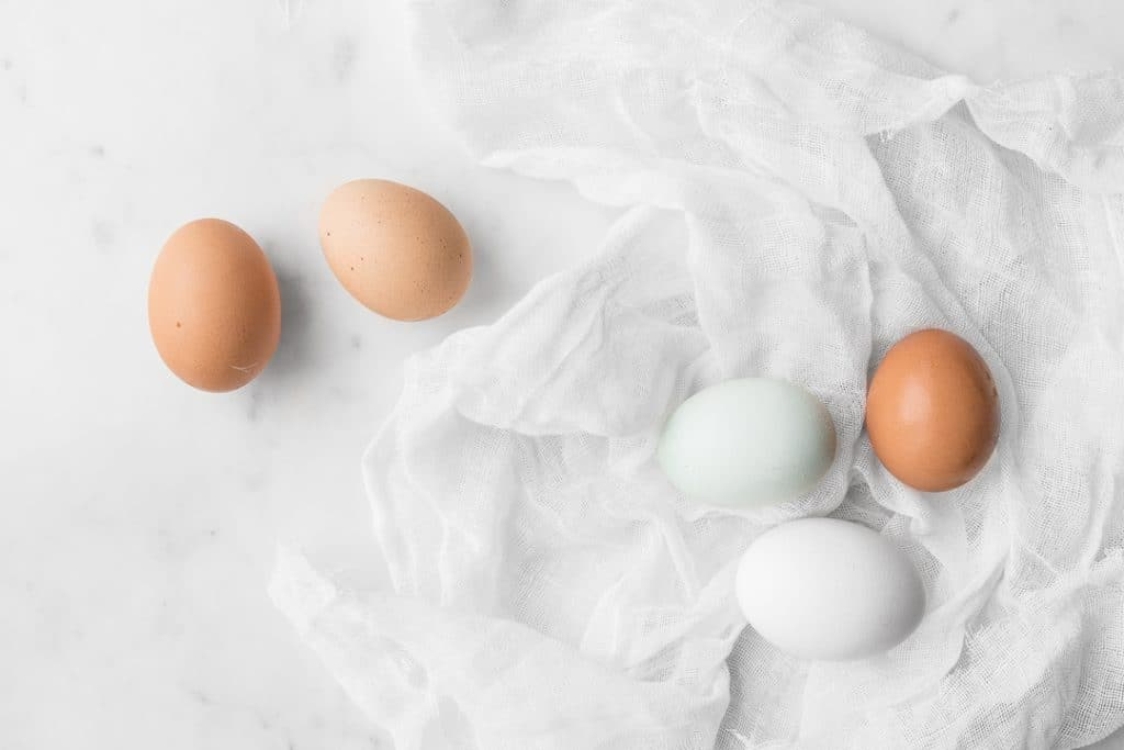 5 eggs laying on white fabric