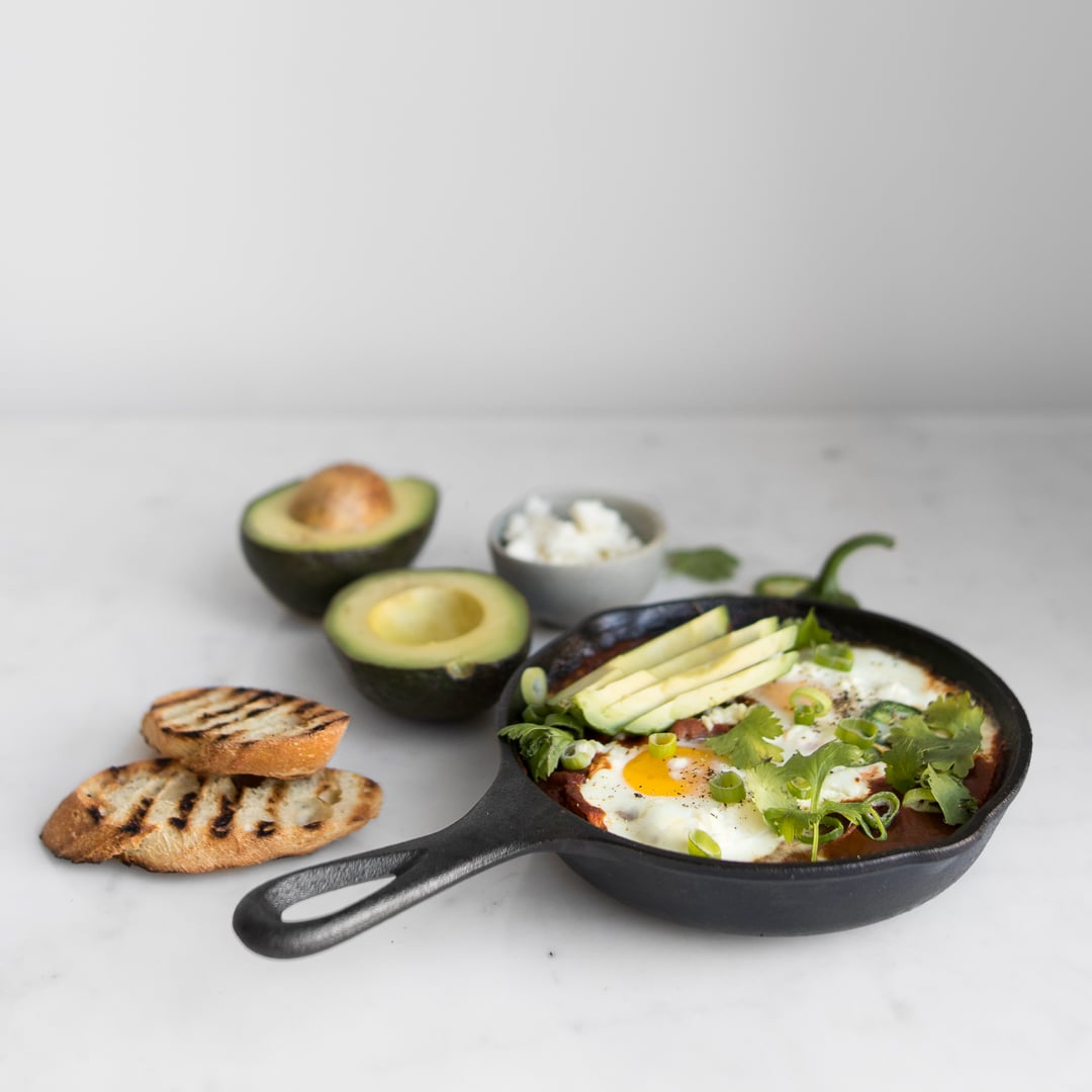 Side view of Vegetarian Shakshuka in skillet next to sliced bread and avocado