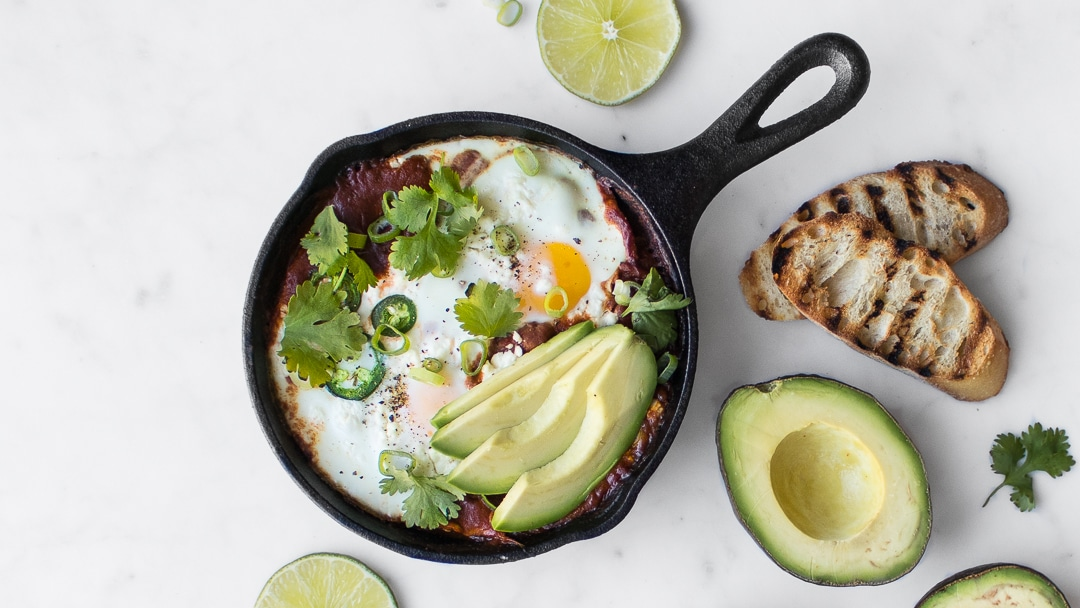 Eggs, sliced avocado, and tomato sauce in black cast iron skillet