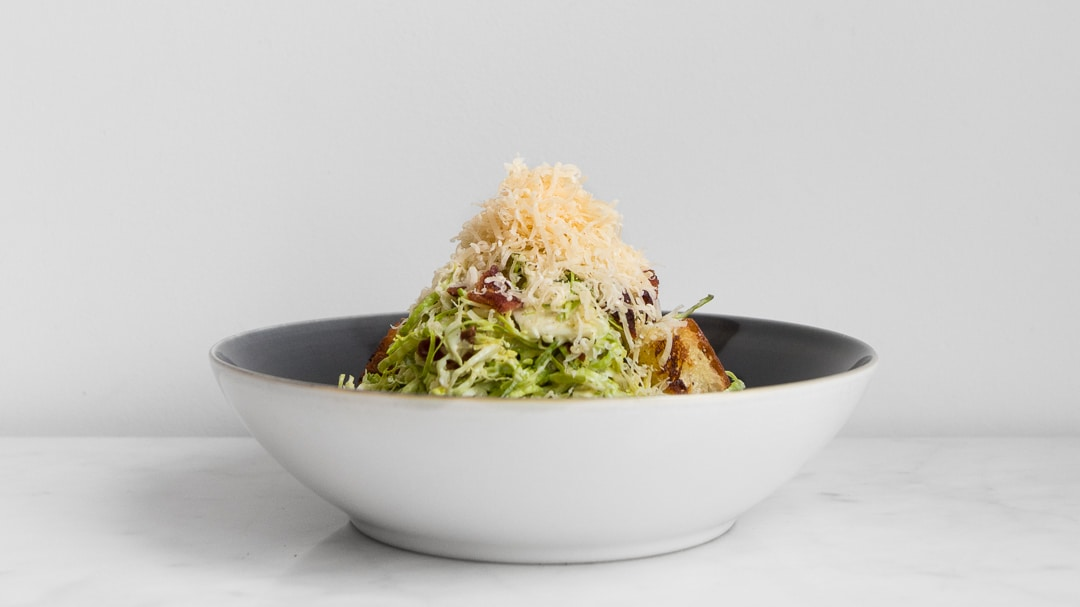 A bowl with filled with brussels sprout caesar salad with grated gouda on top