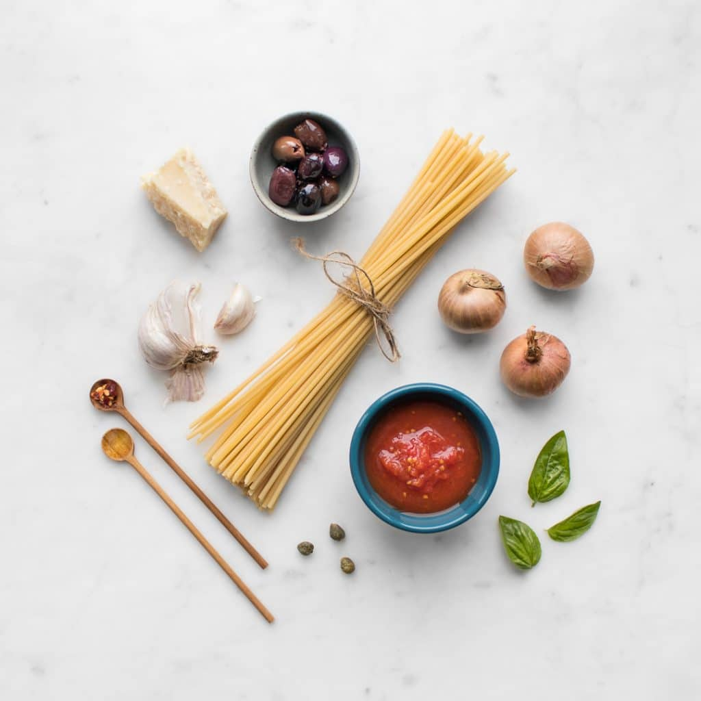 Flat lay of dry spaghetti, tomatoes in a bowl, shallots, garlic, basil, red pepper flakes, olives, parmesan, and capers