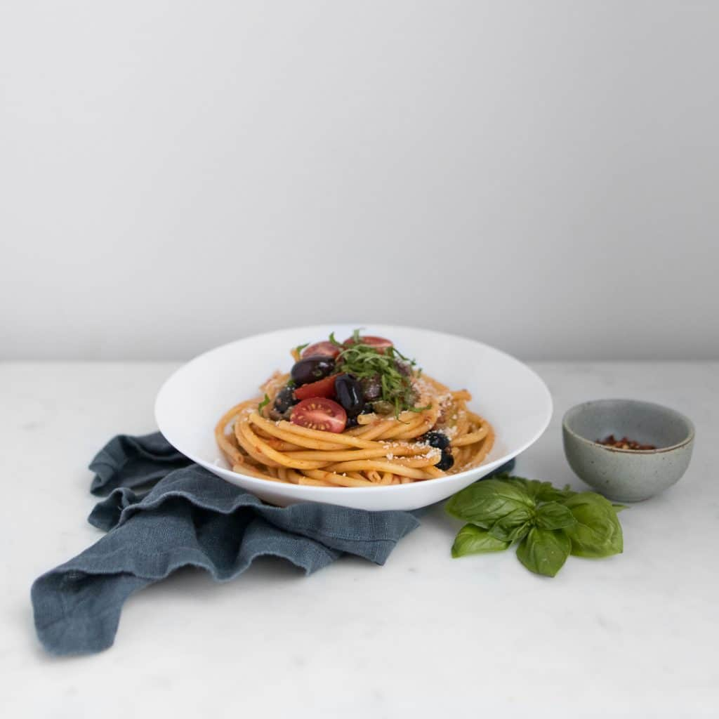 Spaghetti Puttanesca on a white plate with a blue napkin