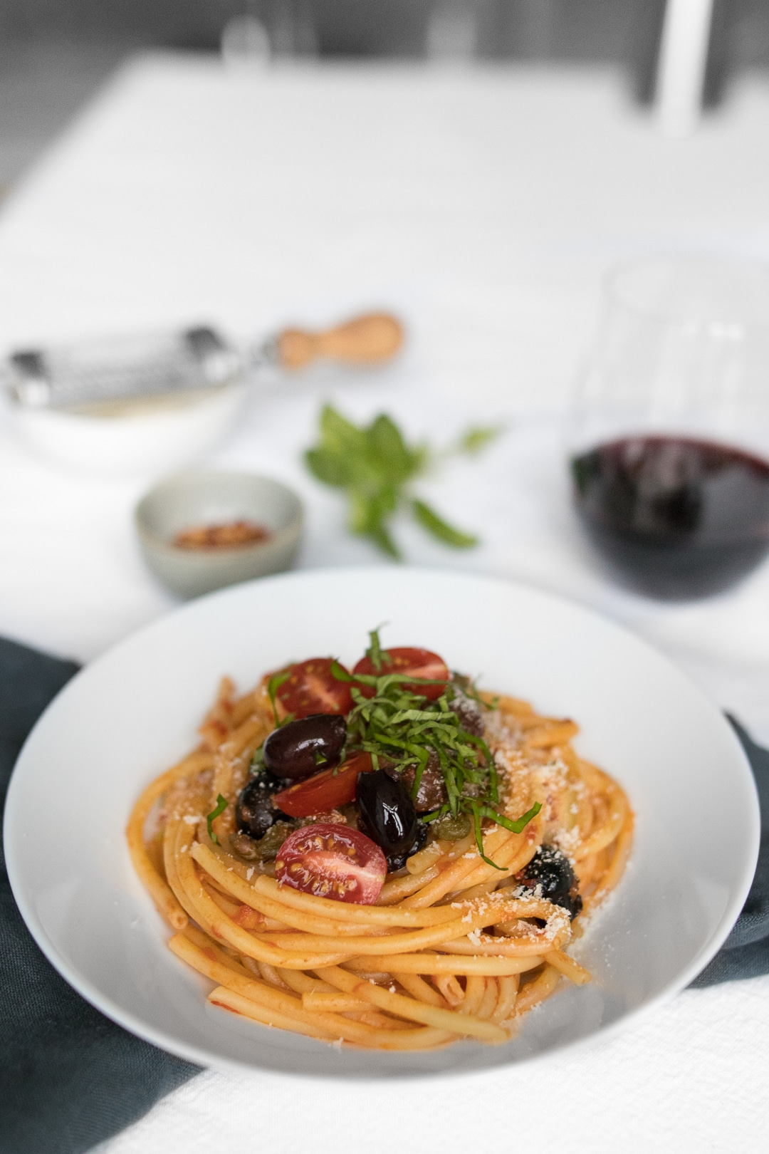 Spaghetti Puttanesca next to a glass of red wine