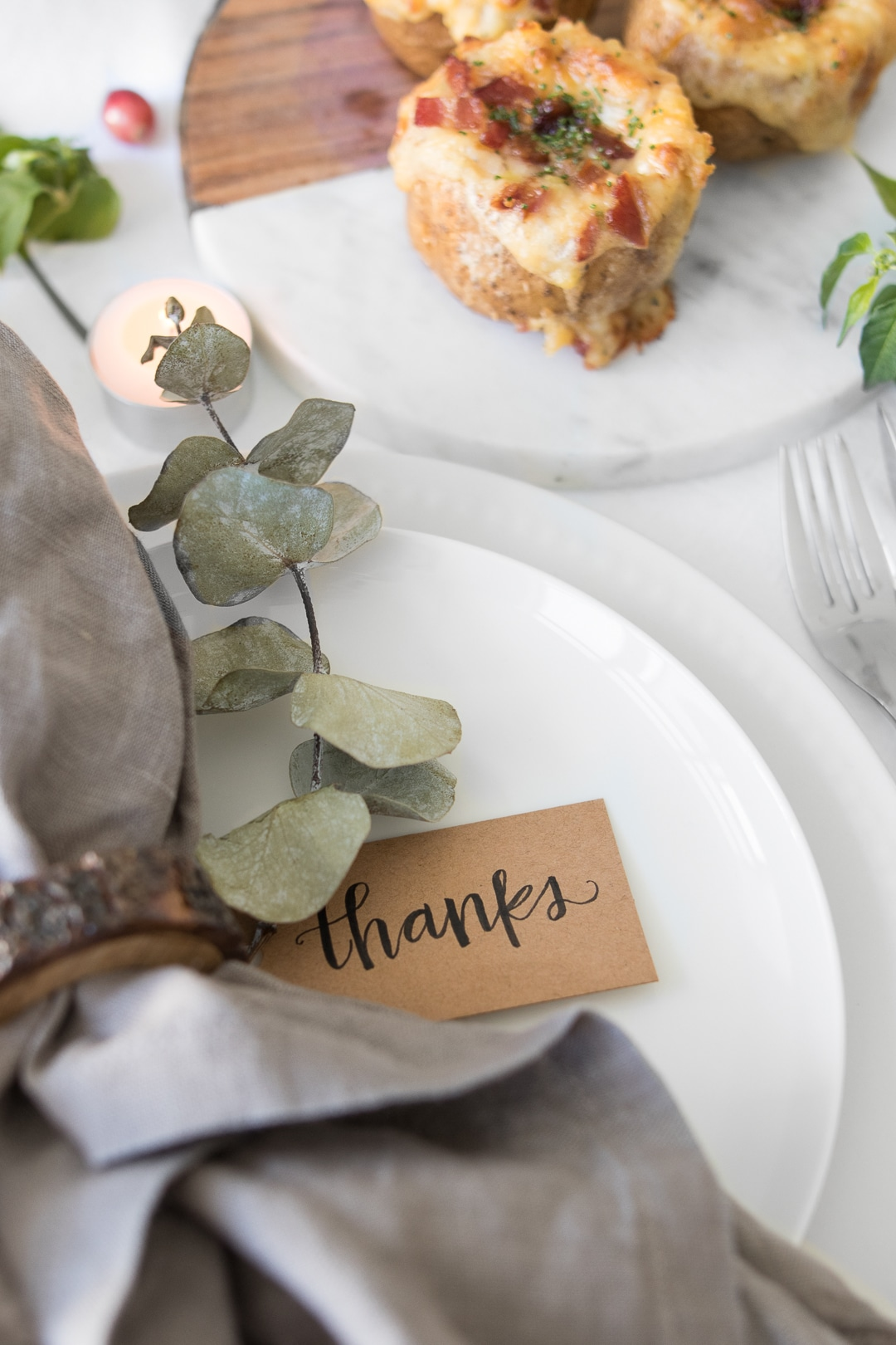 Close up of napkin with Thanksgiving tag and twice baked potato in background