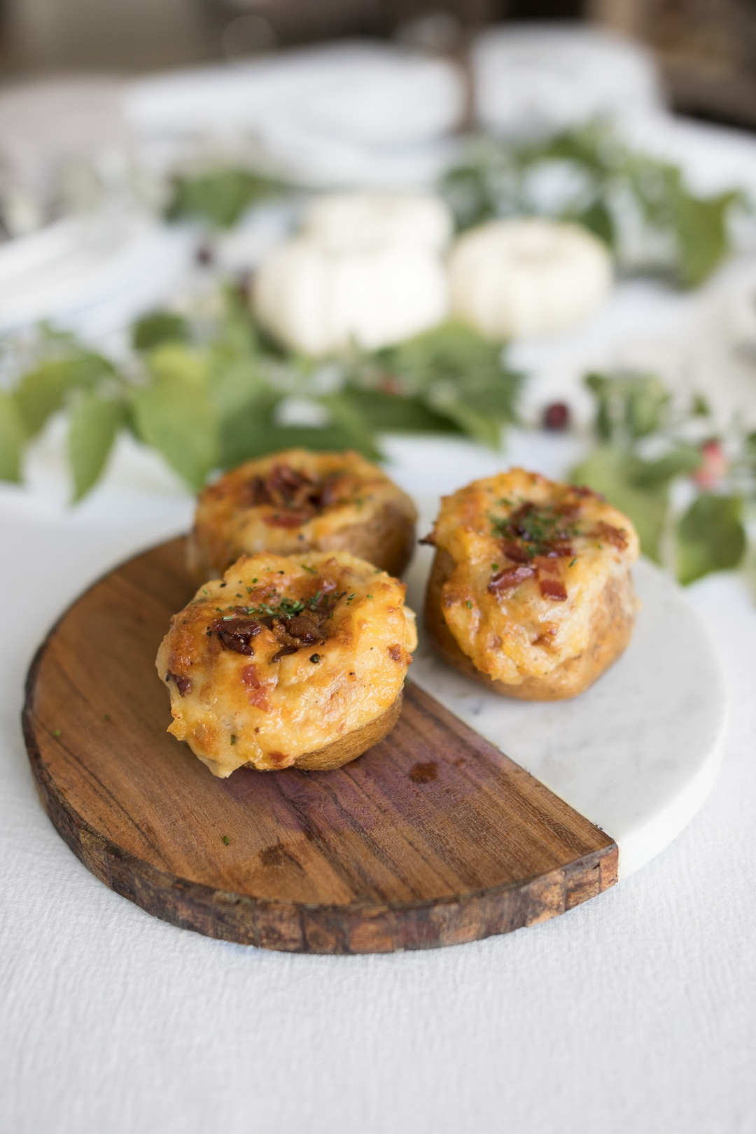 Twice baked potatoes on a wood and marble board