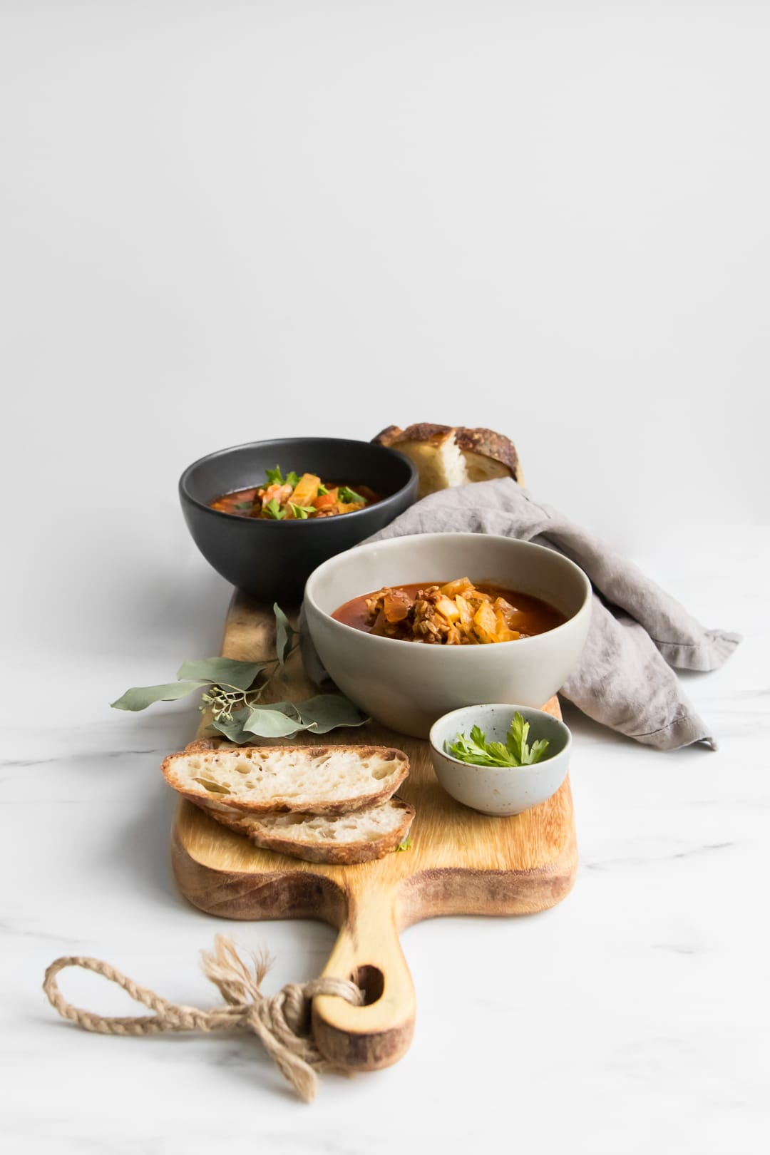 Side view of wooden board with two bowls of Cabbage Roll Stew and two slices of bread