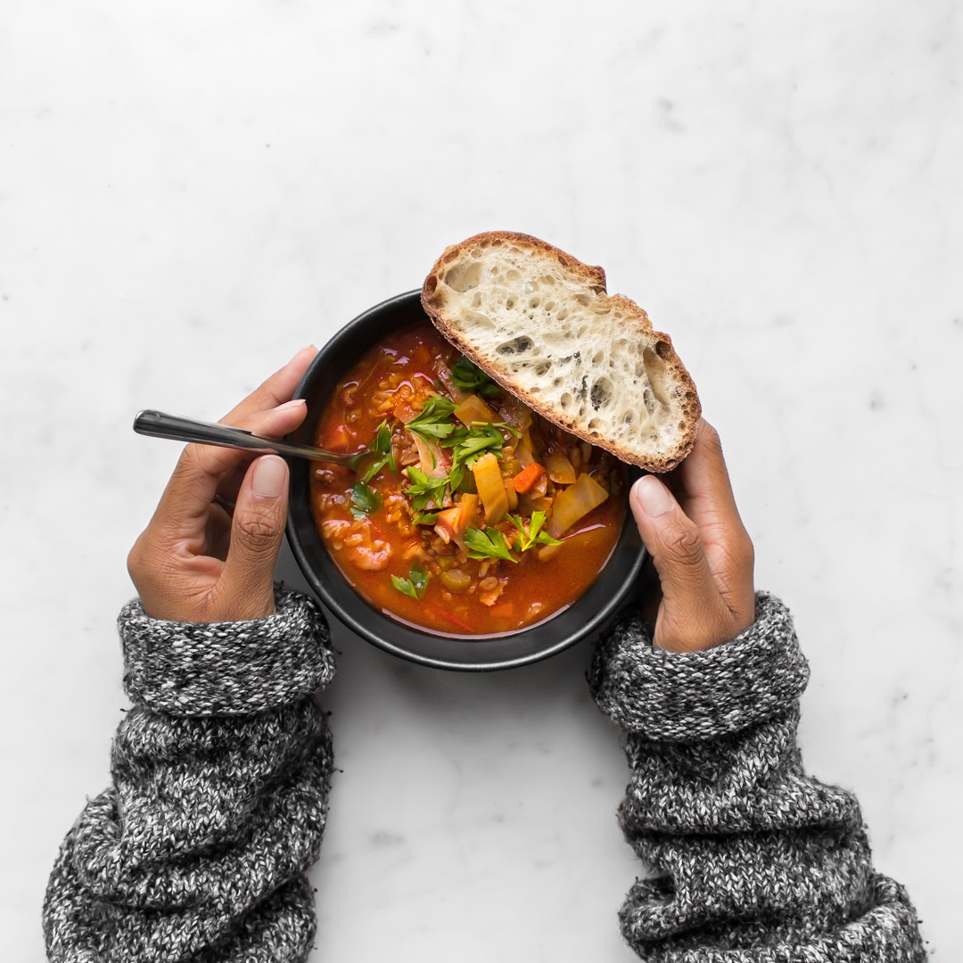 Close up of Mystique's hands holding Cabbage Roll Stew with a slice of bread on the bowl.