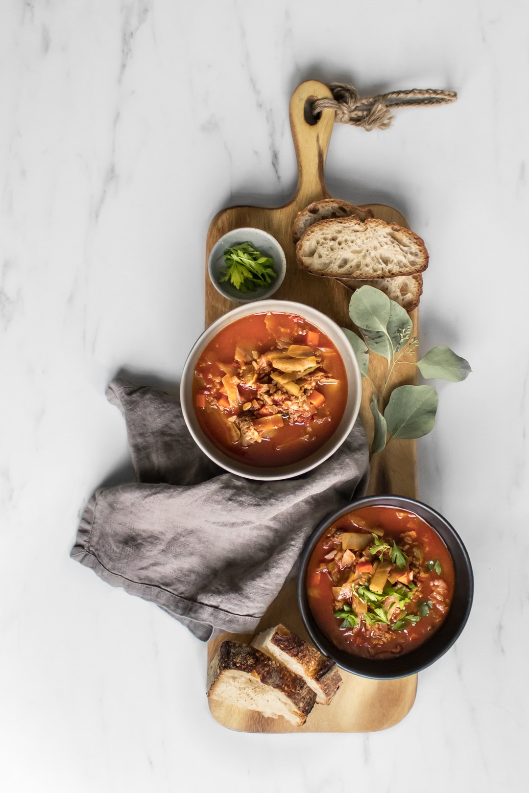 Close up of two bowls of cabbage roll soup on a large cutting board with bread and parsley