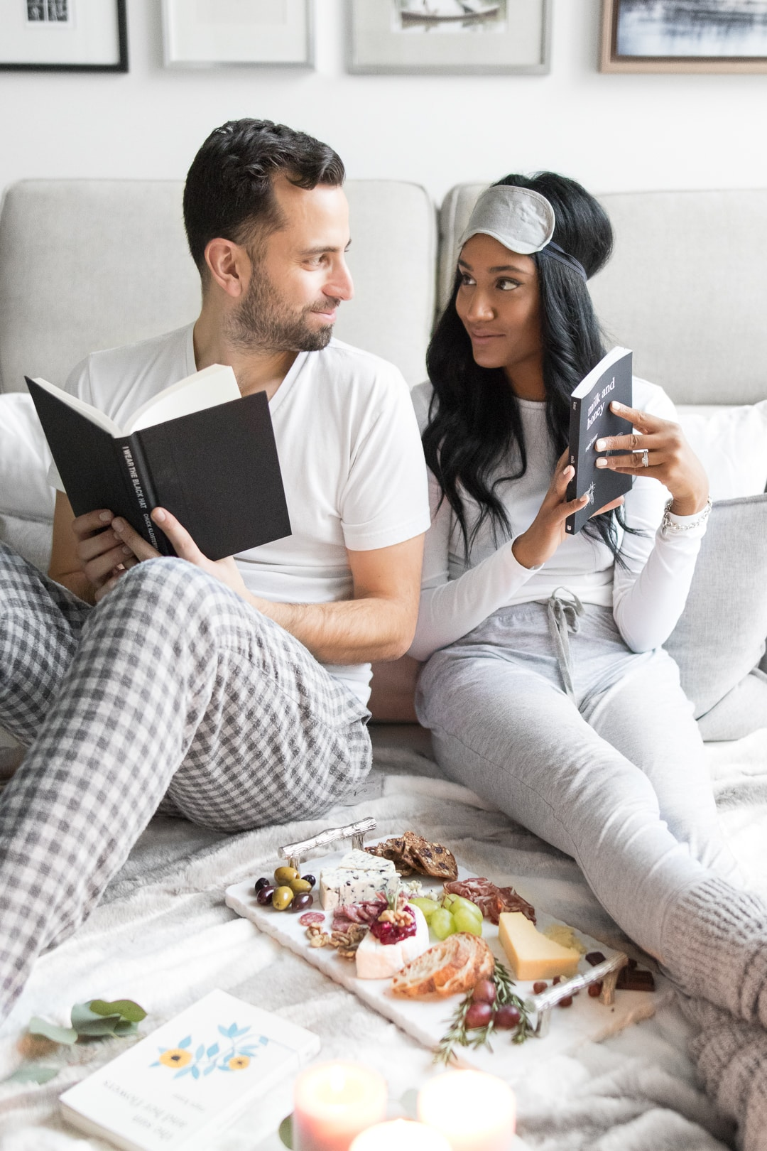 Young couple holding books and looking at each other while sitting next to a comforting cheeseboard.