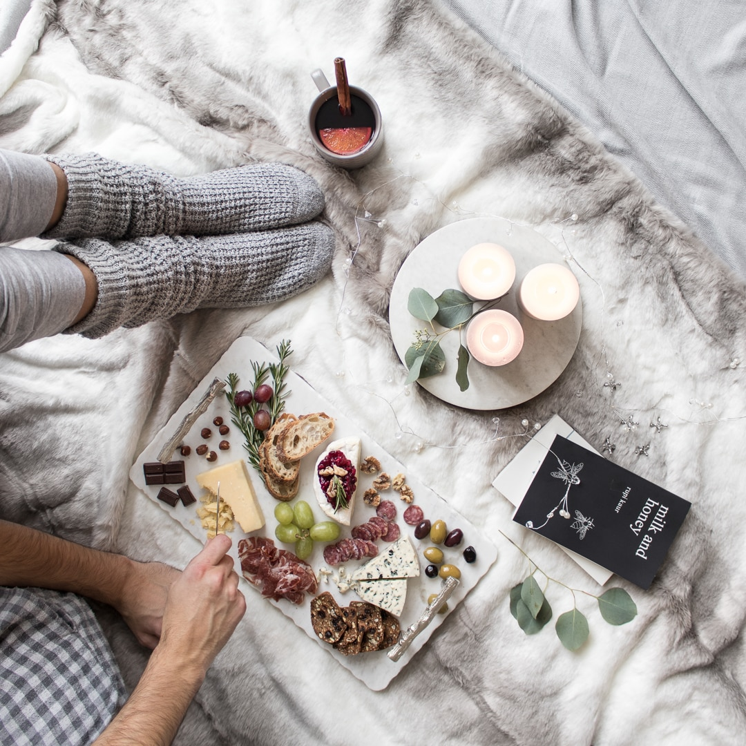 Comforting cheeseboard laying on a blanket on the floor with candles, mulled wine, and books